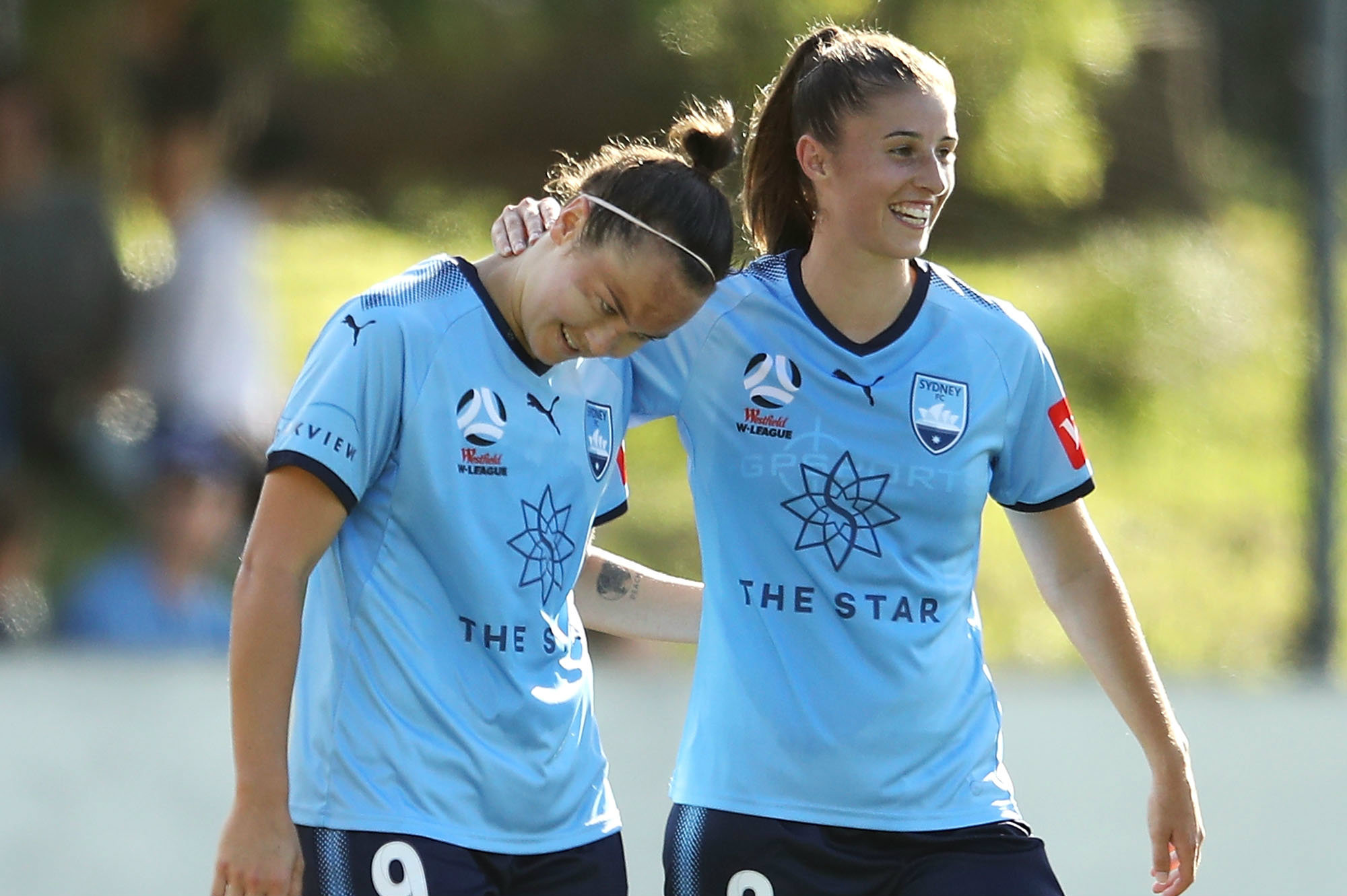 Caitlin Foord and Amy Harrison celebrate a goal against the Roar.