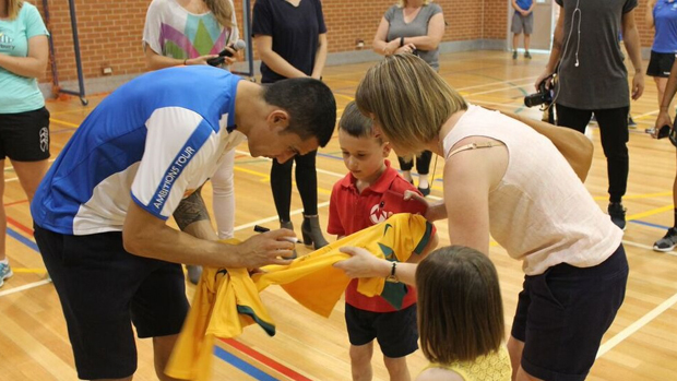 Tim Cahill signs a jersey for a young fan.