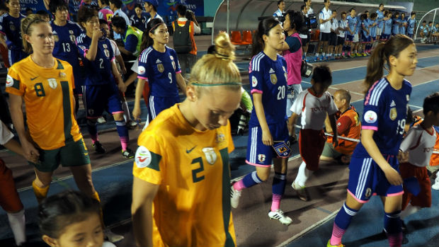 The Matildas and Japan walk out for the 2014 Women's Asian Cup final.2