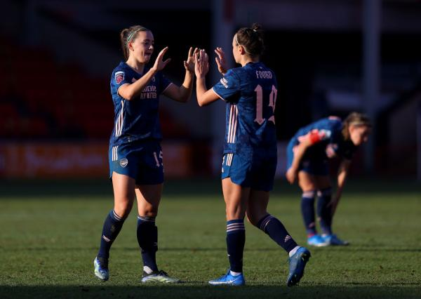 Katie McCabe and Caitlin Foord high five while playing for Arsenal