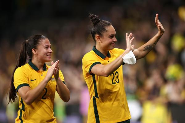 Angie Beard and Emma Checker applaud fans