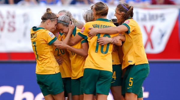 Matildas players celebrate one of Kyah Simon's two goals against Nigeria.