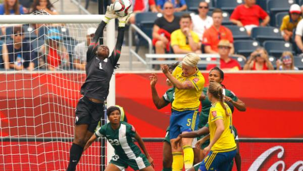 Nigeria's goalkeeper Precious Dede flies high to make a save against Sweden.